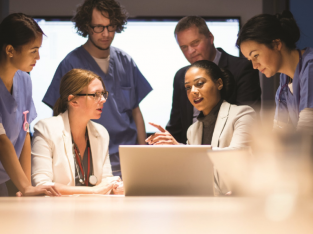 Group of medical professionals having a conversation around a computer